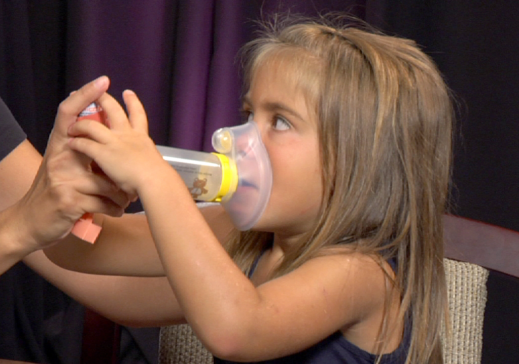 This is a picture of a child with asthma using an inhaler.